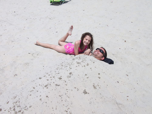 Anna burying Michael in the sand