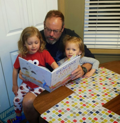 Grandpa reading 'Dragons Love Tacos' (their favorite book) to the girls
