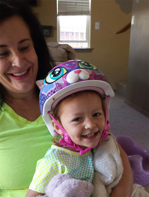Elise trying out her new helmet from Grandma